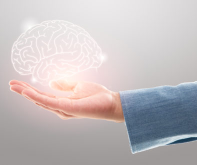 Female doctor holding brain illustration against the gray background. Mental health protection and care