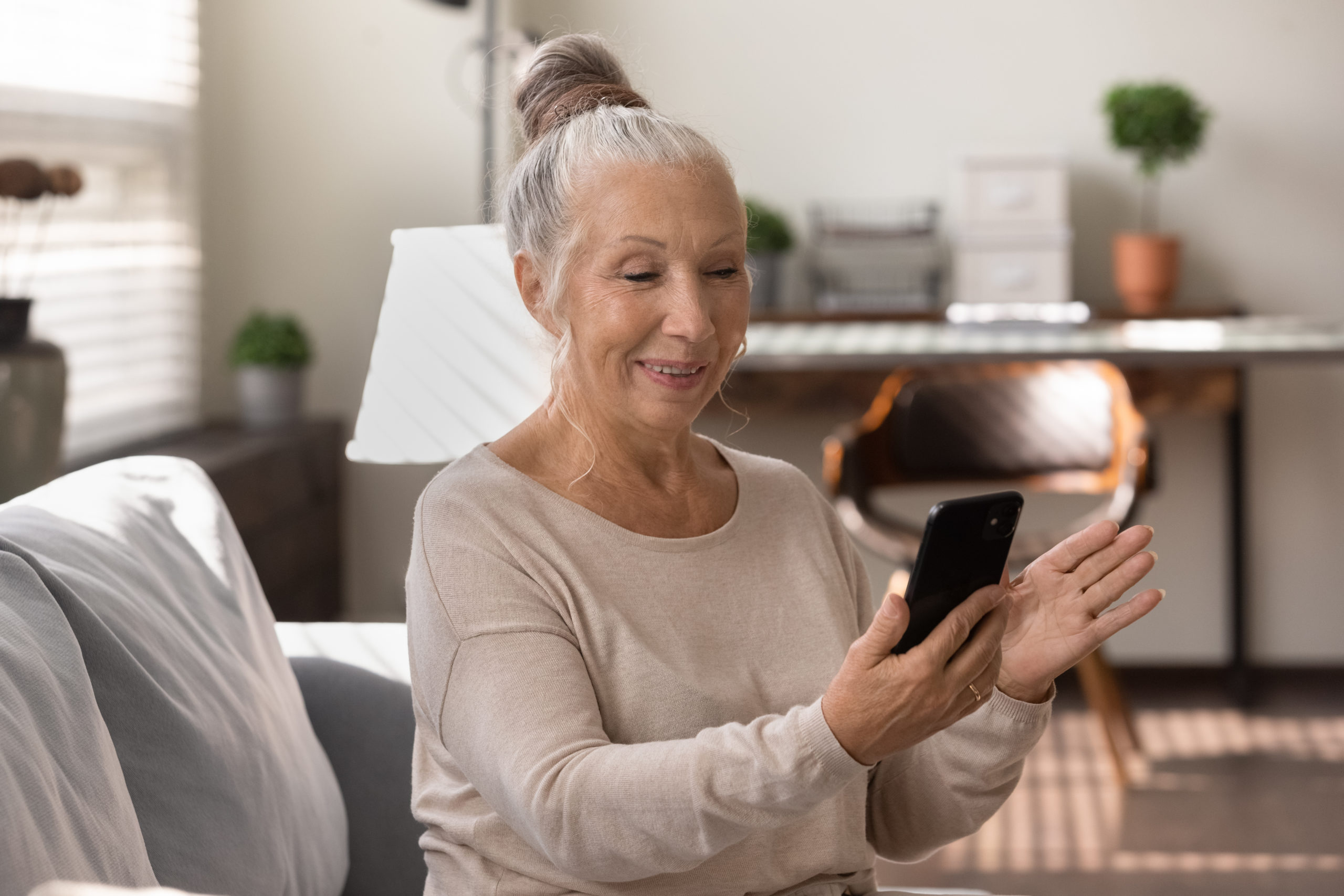 Happy elderly lady using smartphone at home, making video call