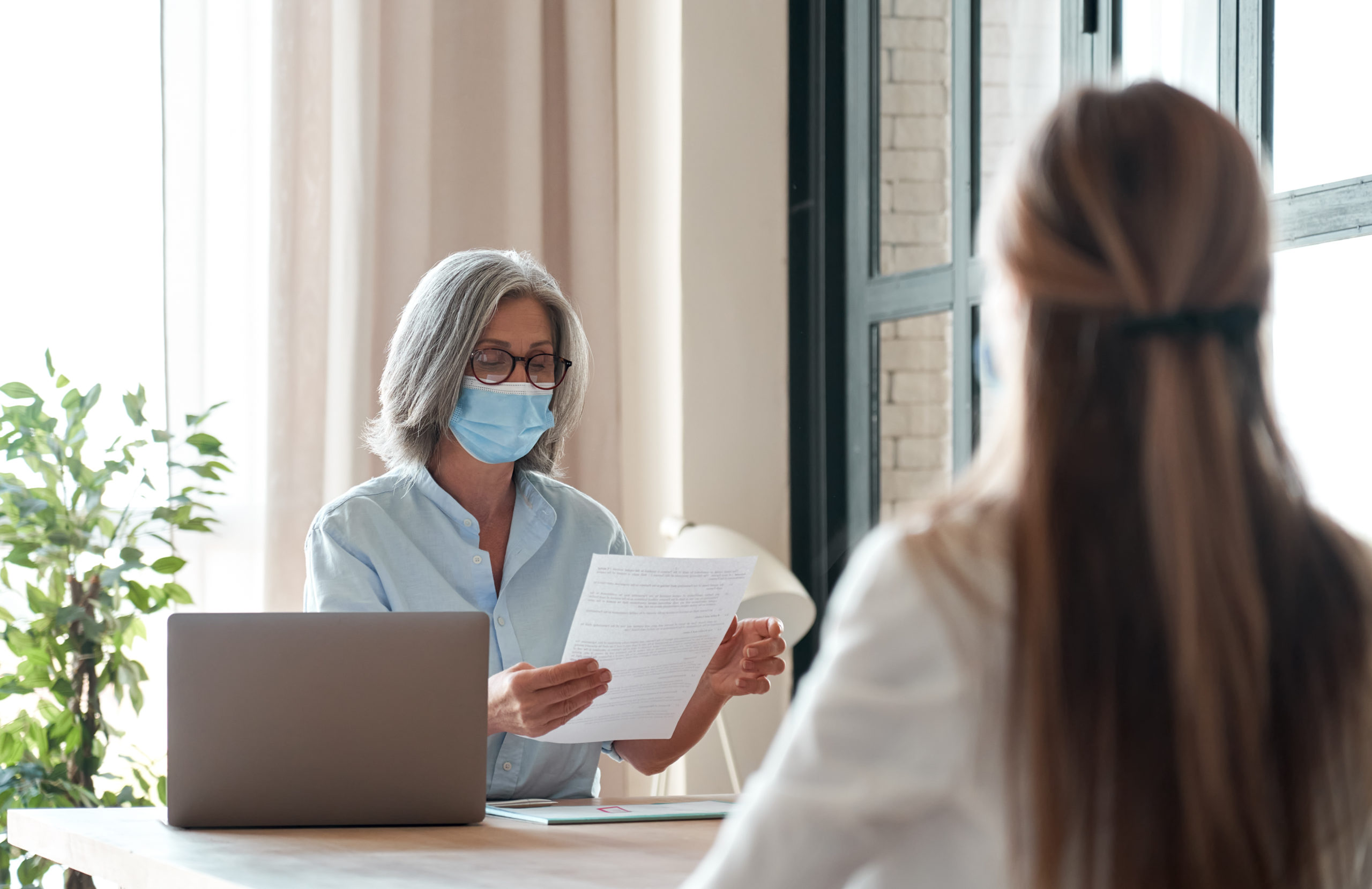 Old hr manager wearing face mask checking female applicant cv at job interview.